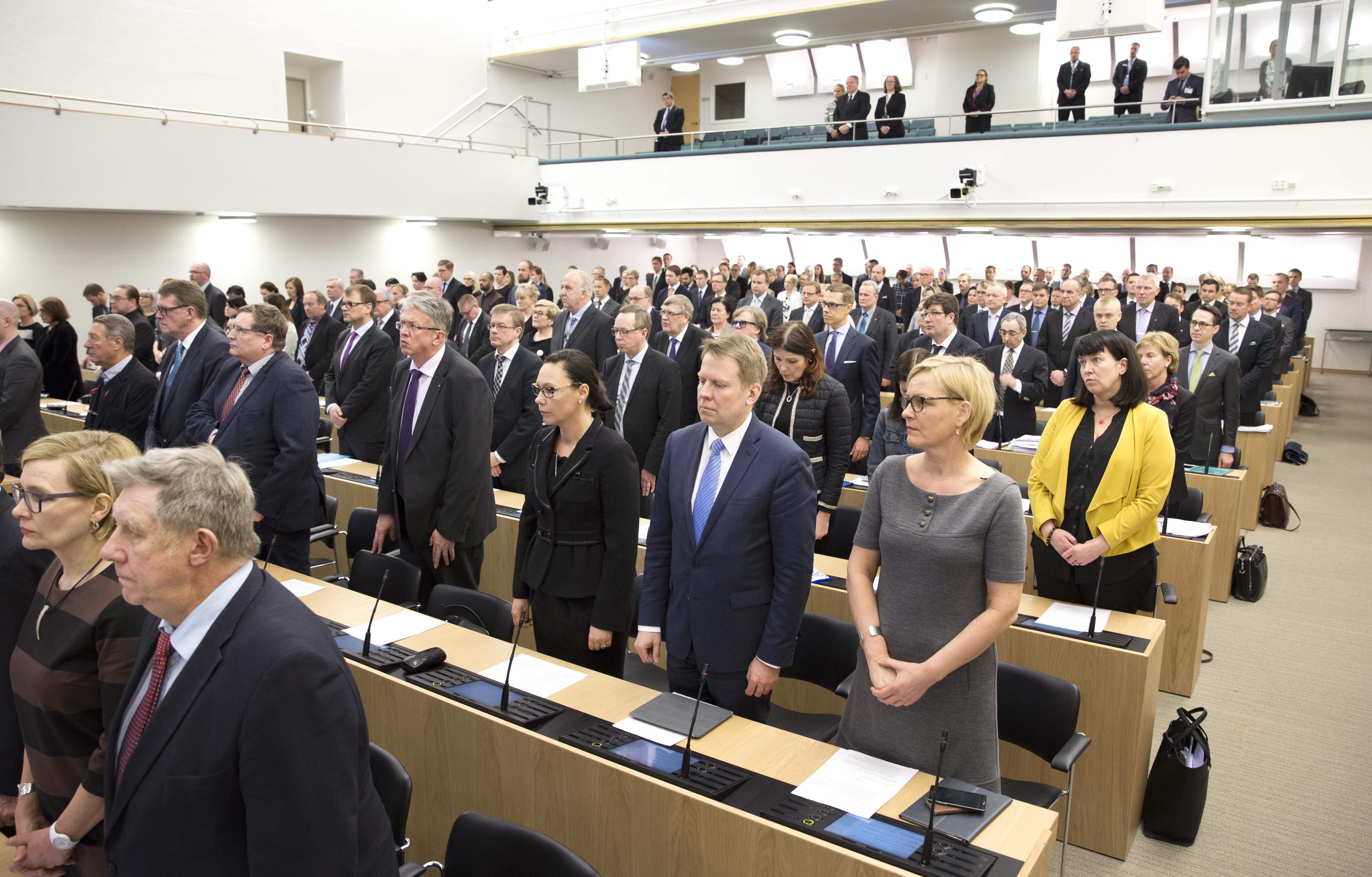 Kansanedustajat seisovat hiljaa Suomen eduskunnan täysistuntosalissa.