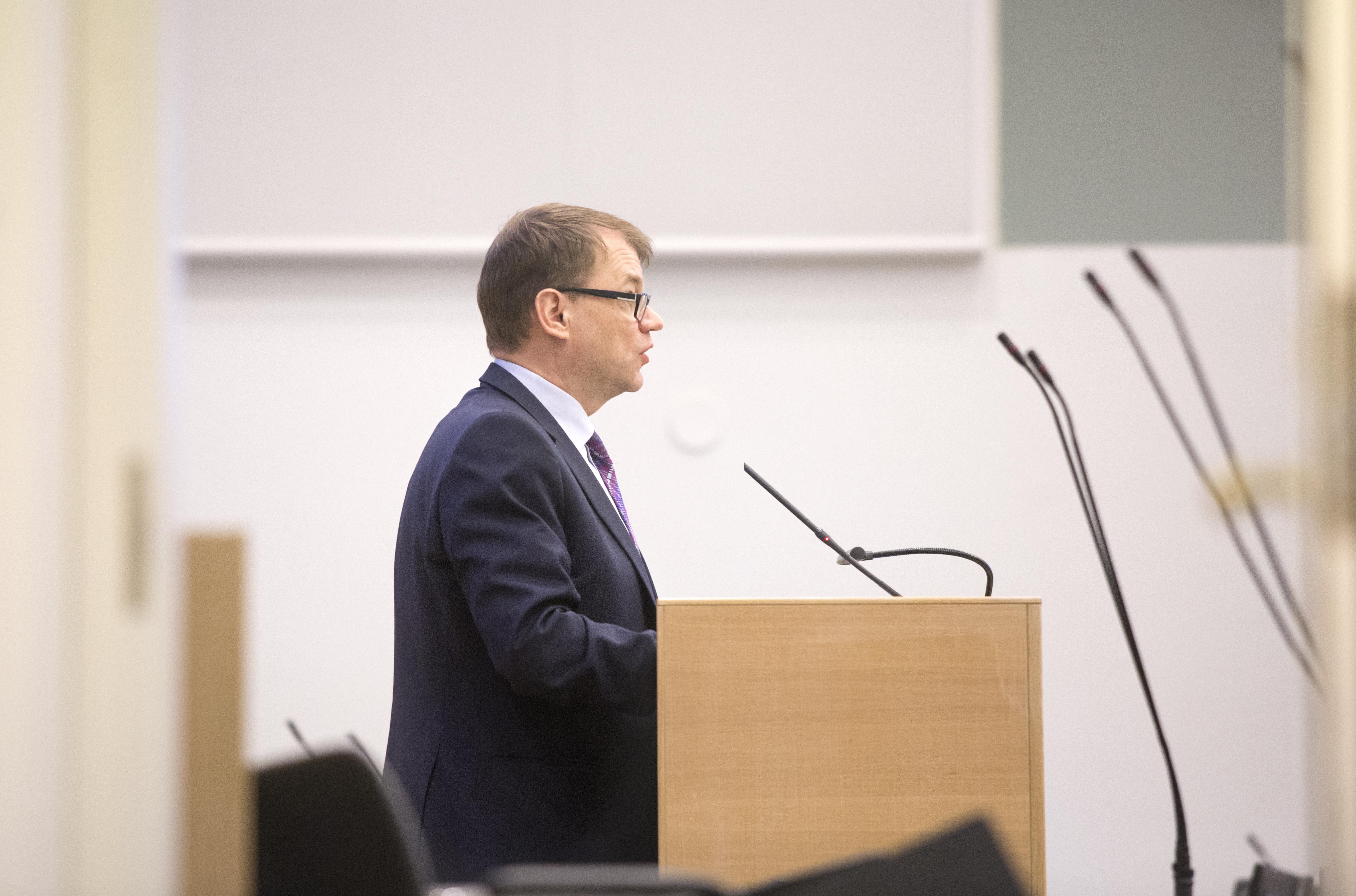 Juha Sipilä seisoo ja puhuu puheenjohtajan pöntössä.