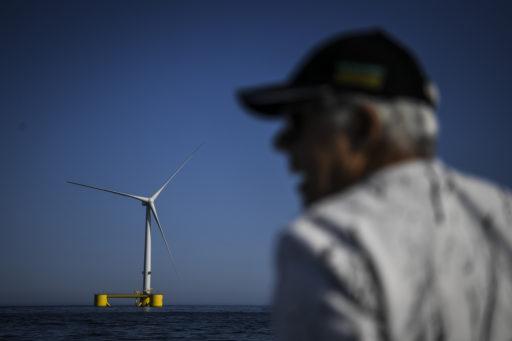 Kuvassa vanha mies ja tuulivoimala merellä.