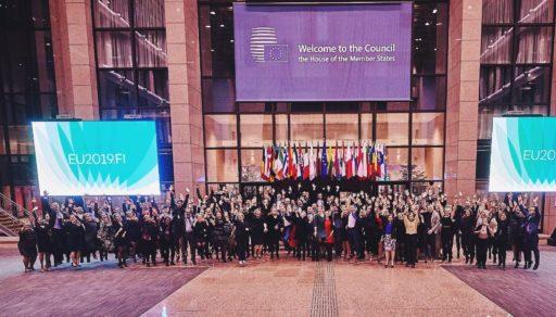 Ryhmä iloisia ihmisiä hyppäämässä ilmaan Euroopan unionin neuvoston rakennuksen aulassa.